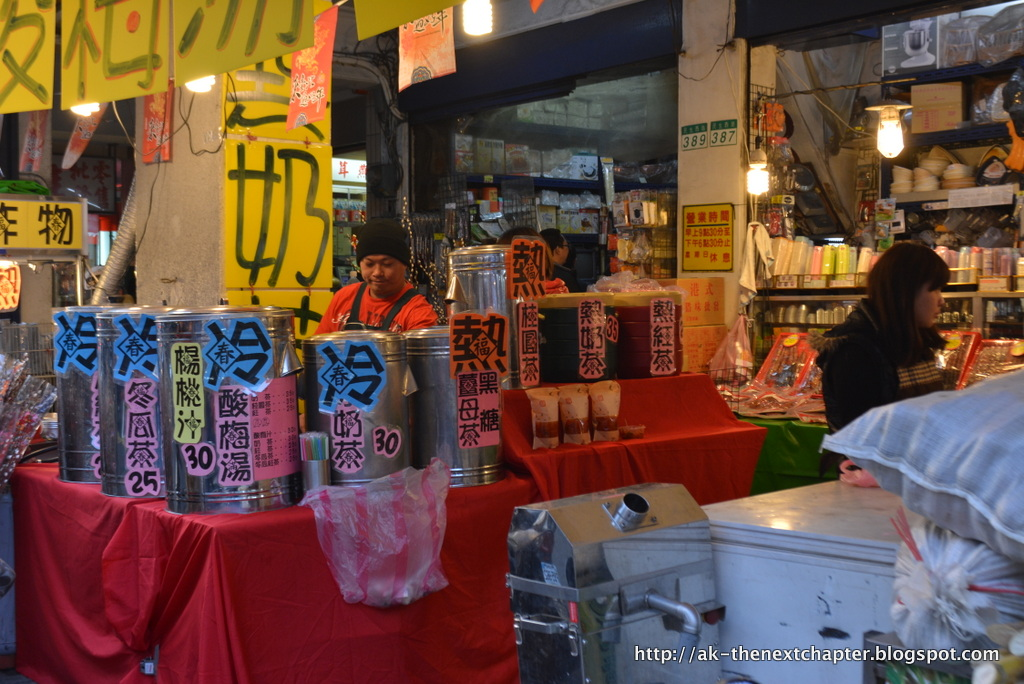 Taiwanese market stand, full of jars with colourful food and signs in chinese