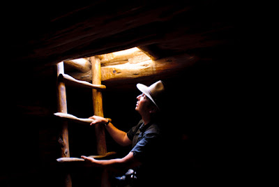Daylight bathes Jeremy Wade Shockley as he climbs out of a kiva at Mesa Verde National Park.