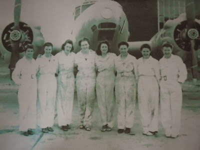 Eight female mechanics standing in front of a WWII airplane
