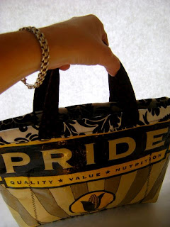 A hand holding the black handles of a bag that is predominantly yellow and black. The inside is a very striking black leaves/floral pattern on white. The outside of the bag says Pride in big yellow capital letters against a black background at the top. In much smaller letters below, in black on gold, it says quality & value & nutrition. Near the bottom of the bag in the center is an ear of corn surrounded in a gold circle. There are rays like sun rays coming up from the bottom in alternating yellow and faded black over yellow. The overall effect is very bold and striking.