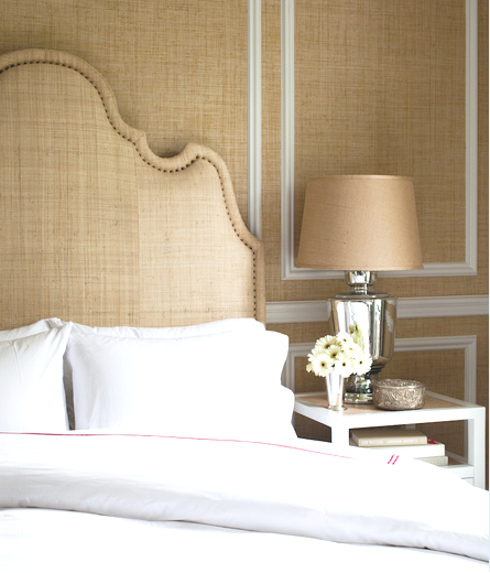 Bedroom with Seagrass walls, raffia headboard and white nightstand with raffia accents