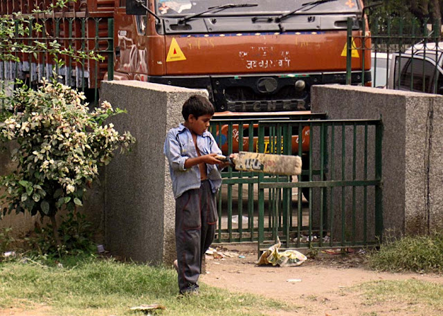 child batting while playing cricket