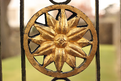 A multi-petaled flower in a circle painted gold, part of a gate at St Fagans.