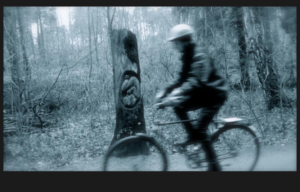Polkupyöräöijä ohittaa sikiön puunrunkoon veistettynä
