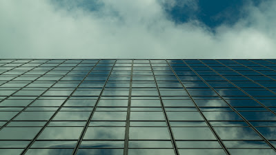A generic corporate office building mirroring the sky in it's expansive array of glass windows