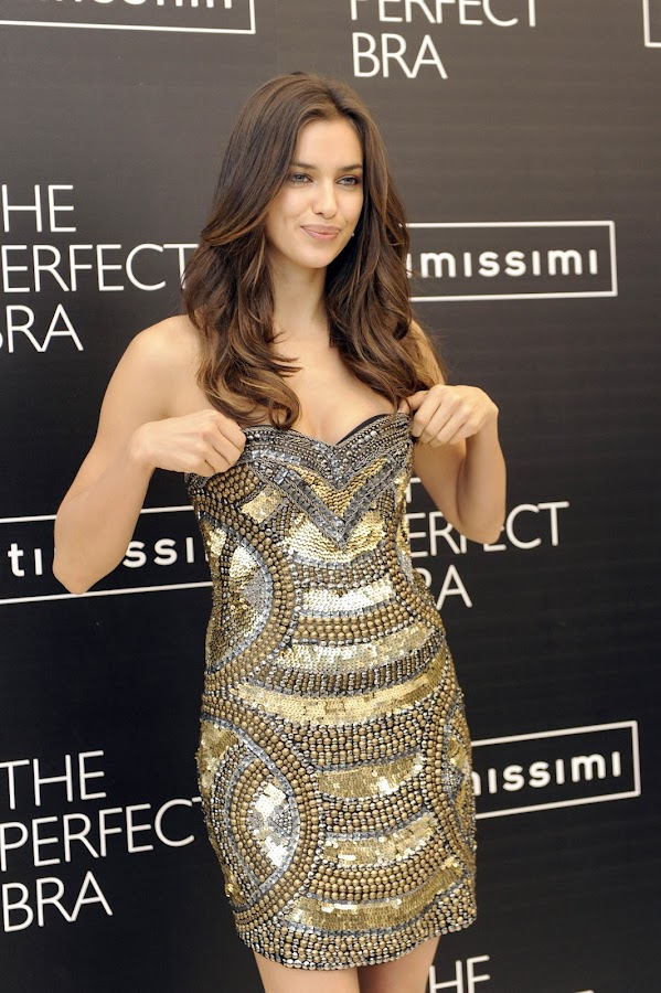 Irina Shayk readjusts her dress  as it slipped