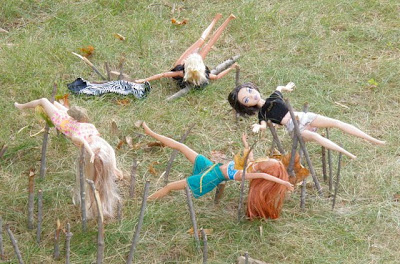 barbies on sticks found in a yard