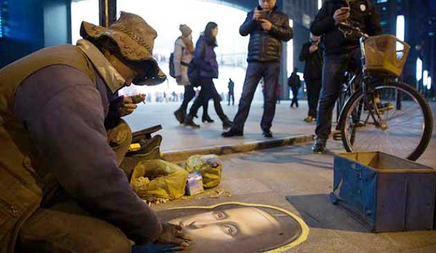 Pengemis yang melukis dengan kapur tulis di trotoar
