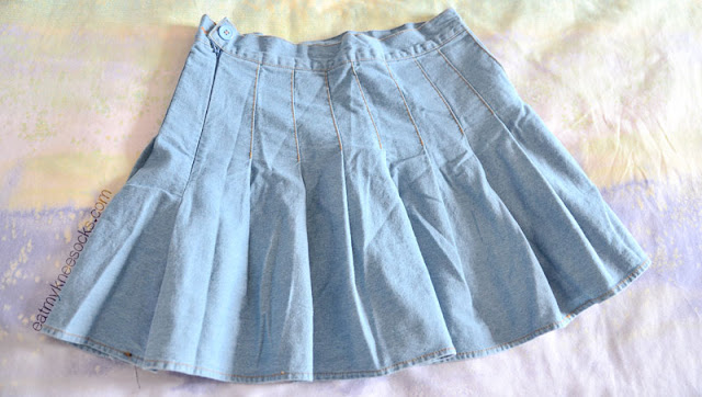 SheIn's pleated denim skirt is a style dupe of the popular American Apparel pleated tennis skirts, but made from a different, unique fabric.