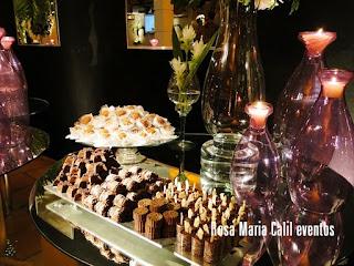 doces, vidros roxos com velas, chocolate, bandeja de prata, parede preta com espelhos
