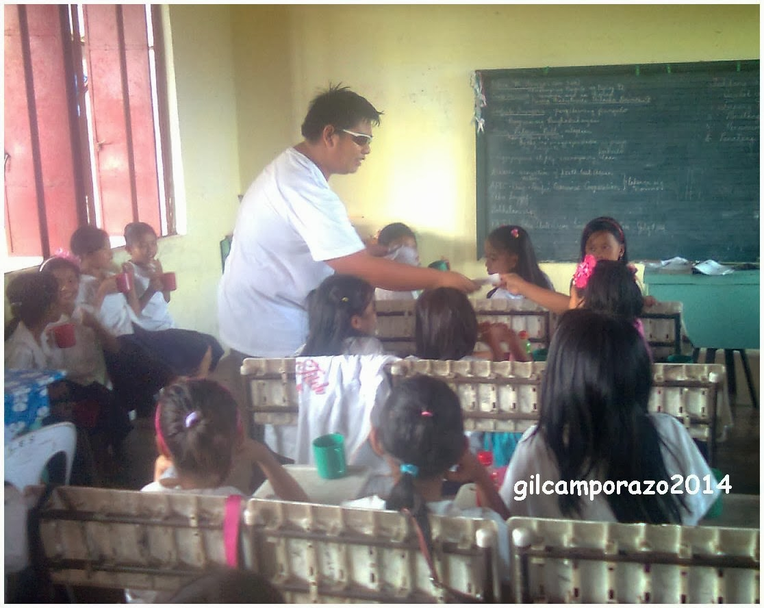 Dr. Corgos giving deworming medicine to grade V pupils