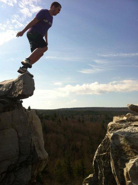 Homem pulando de lugar alto