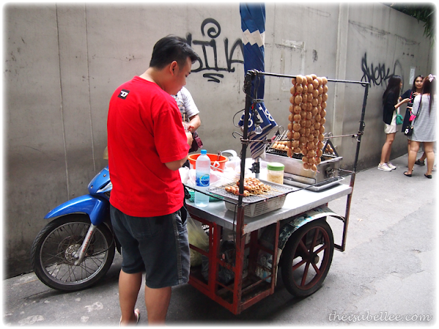 Buying sausages on the roadside in Bangkok Thailand