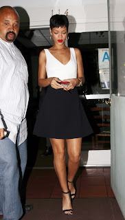 Rihanna looks great in a black skirt and white top