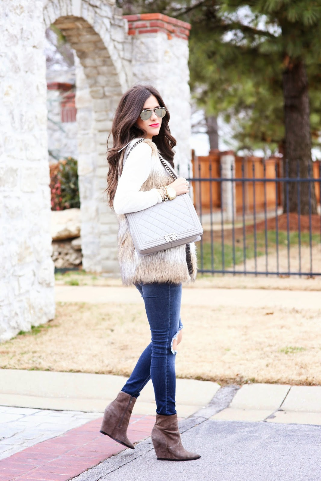 faux fur vest, chic wish fur vest, ripped jeans, knee ripped jeans, grey chanel boy bag, the courtey bibb, bauble bar courtney bib with pearls, emily gemma, cream v neck sweater, michael hors runway watch in gold, david yurman black onyx ring, david yurman ring, mirrored rayon aviators