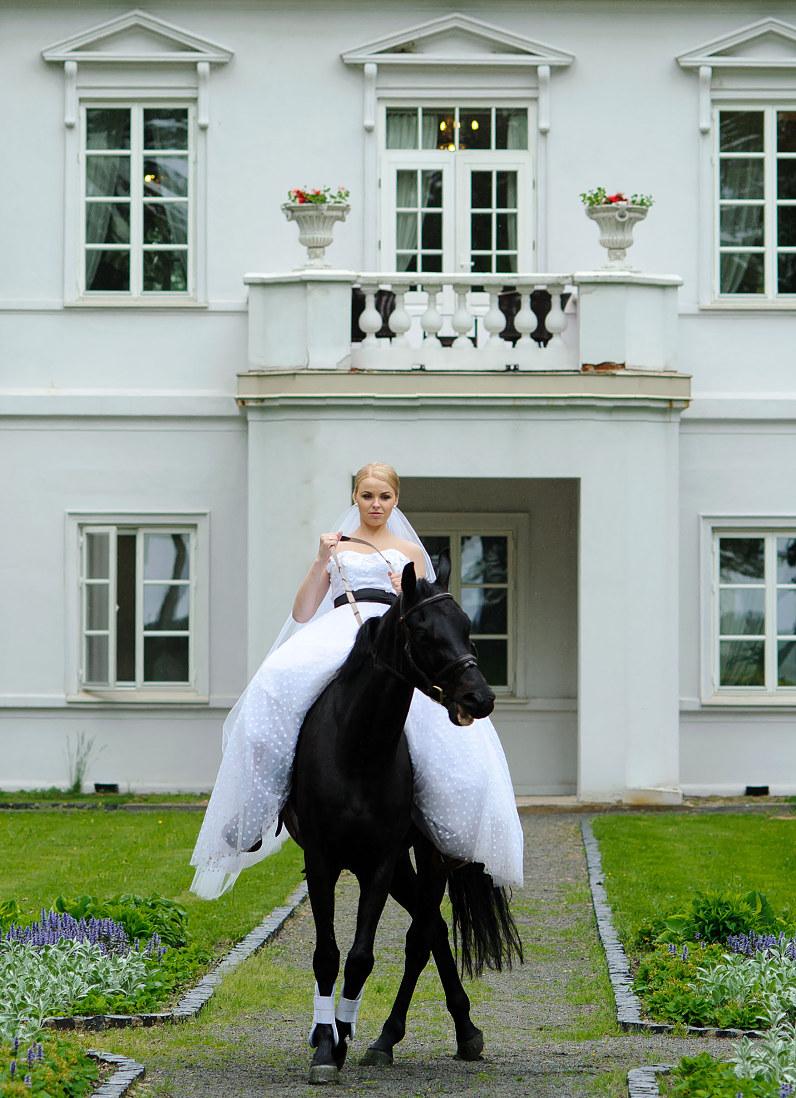 vestuvių fotosesija su žirgais ir nuotaka ant arklio bistrampolio dvare