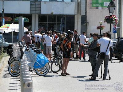 Проезжий велосипедист дает интервью на открытии платной парковки велосипедов