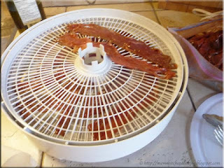 loading the dehydrator trays with marinated beef strips