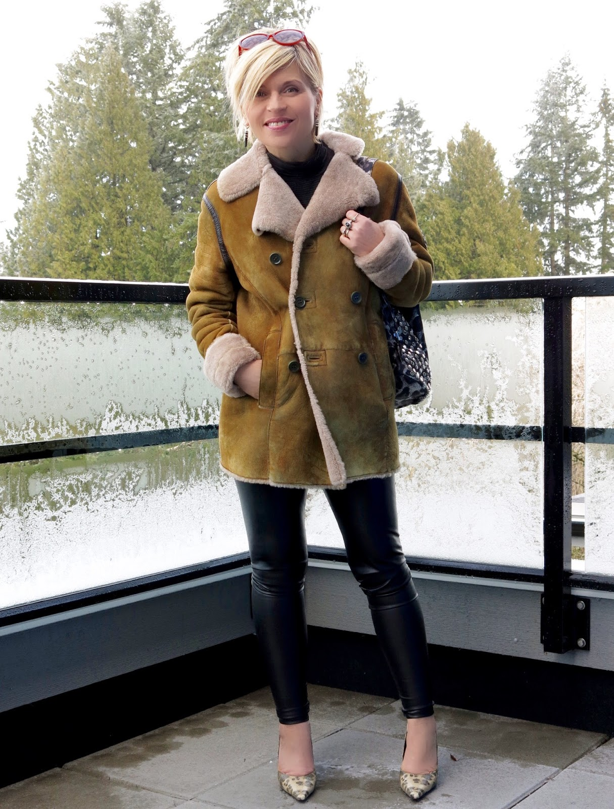 styling a sheepskin coat with faux-leather leggings, reptile pumps, and cat-eye sunglasses