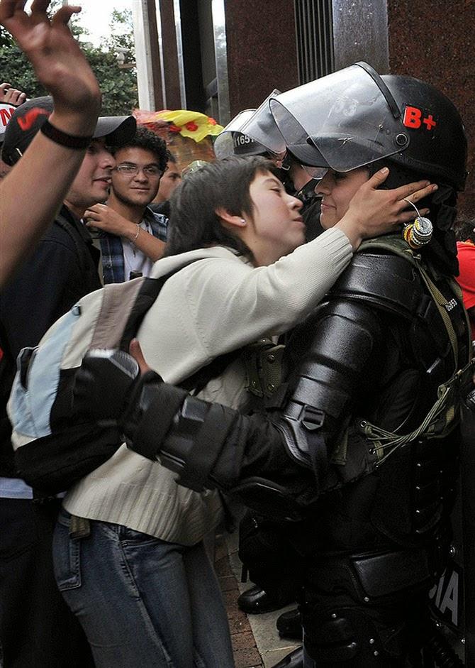 Демонстрантка пытается поцеловать полицейскую во время студенческого протеста в Боготе, Колумбия, 2011 год.