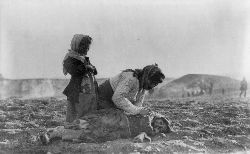 Syria, Aleppo. Armenian woman kneeling beside dead child in field within sight of help and safety at Aleppo.