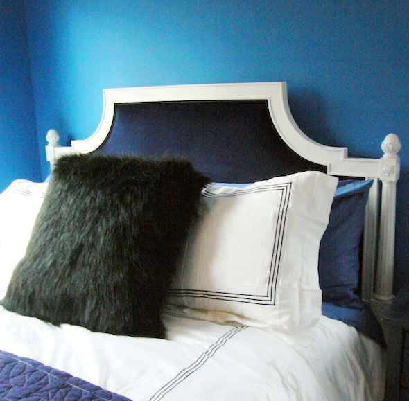 The refurbished white and blue velvet headboard in a blue boys room with white sheets with navy piping and a furry accent pillow