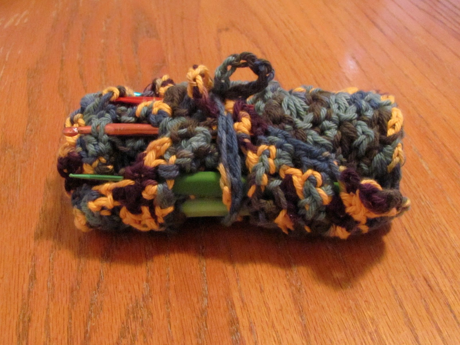 Multi-colored home made crochet hook case rolled up for storage