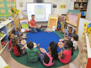 Alex dá aula para as crianças sentadas no chão.  Foto de Carla Guarilha.