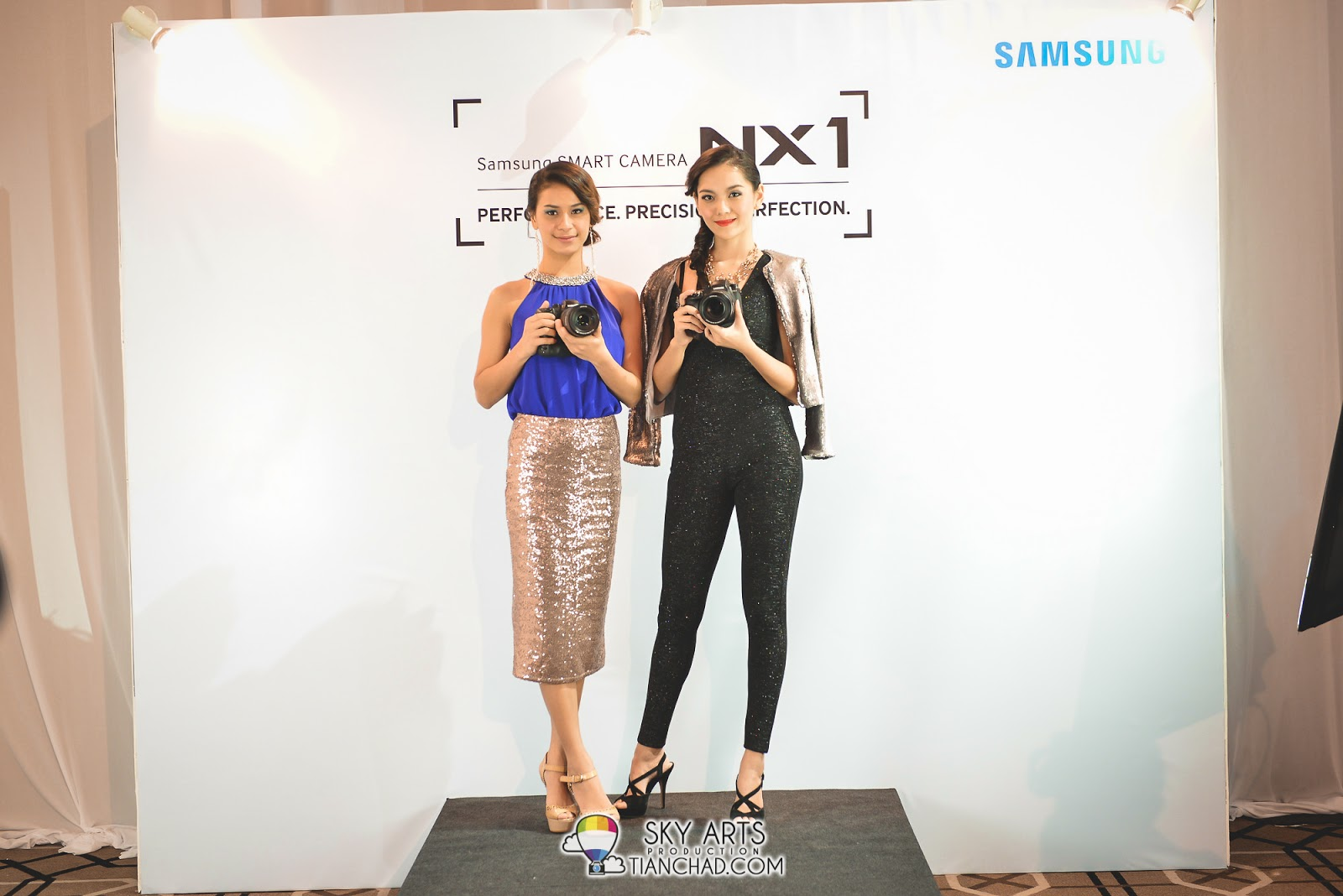 Two gorgeous models holding the Samsung NX1