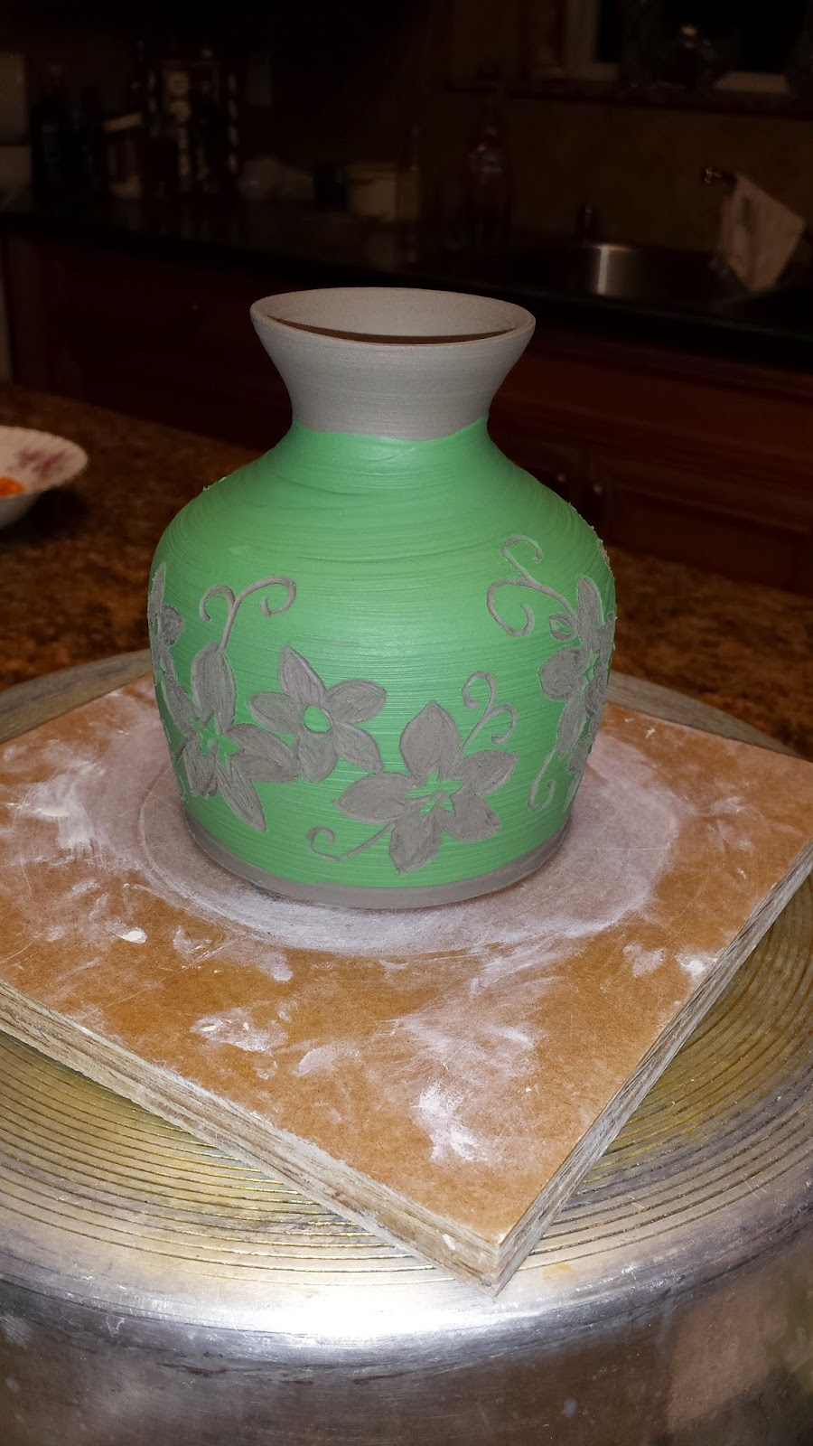 Sgraffito white flowers on green vase, ceramic / pottery in progress.