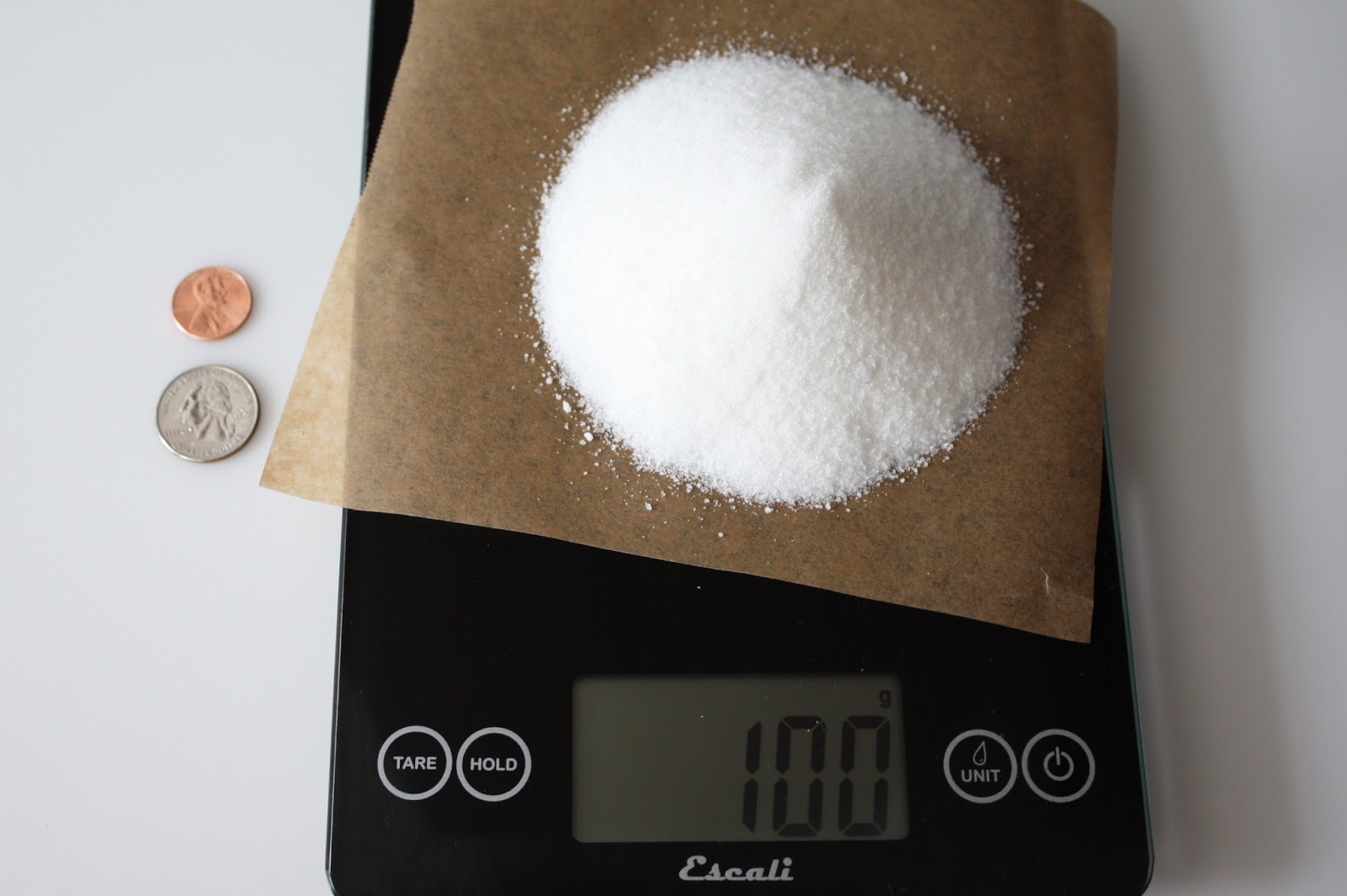 100 grams white granulated sugar on a scale with coins for visual comparison