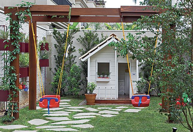 banco de jardim infantil:esta área infantil no jardim. O pergolado sustenta os balanços de