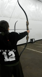 the back of a female presenting person with long braided dark brown hair. She is pulling an arrow on a left handed recurve bow and her back is to the camera. her jacket is black and says EVERDEEN on it, letter jacket style. The letters are in an arc above a large number 12