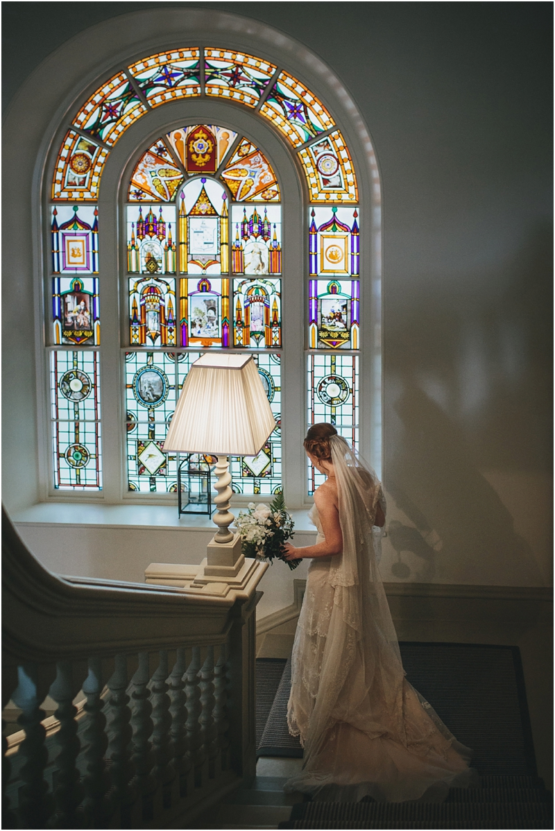 Bride going down the stairs with a stained glass window