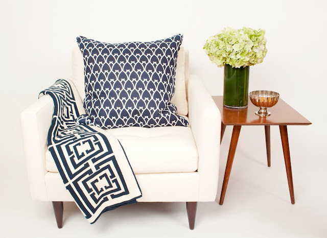 COCOCOZY Logo Throw in navy on a white chair with a COCOCOZY pillow in Navy and a wooden side table with hydrangeas