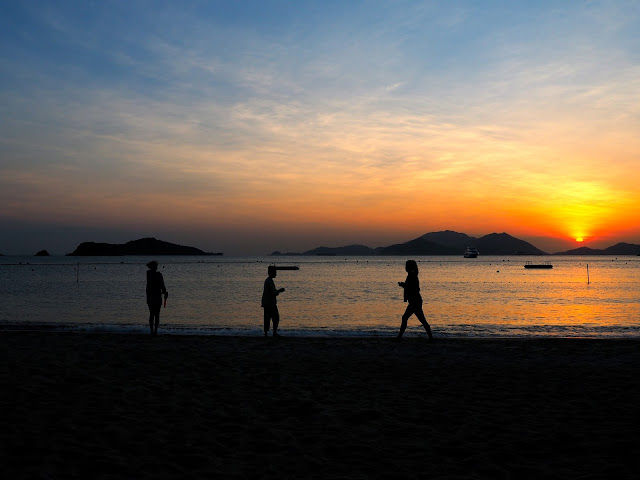 Silhouettes of three girls on the sand against the sunset over the ocean on Repulse Bay Beach, Hong Kong