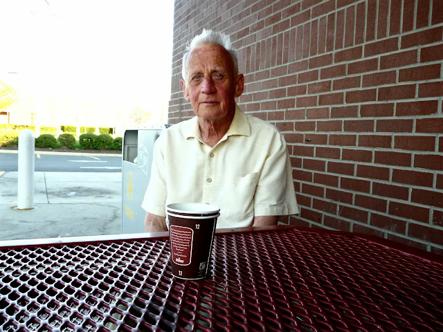 man at outdoor table with coffee