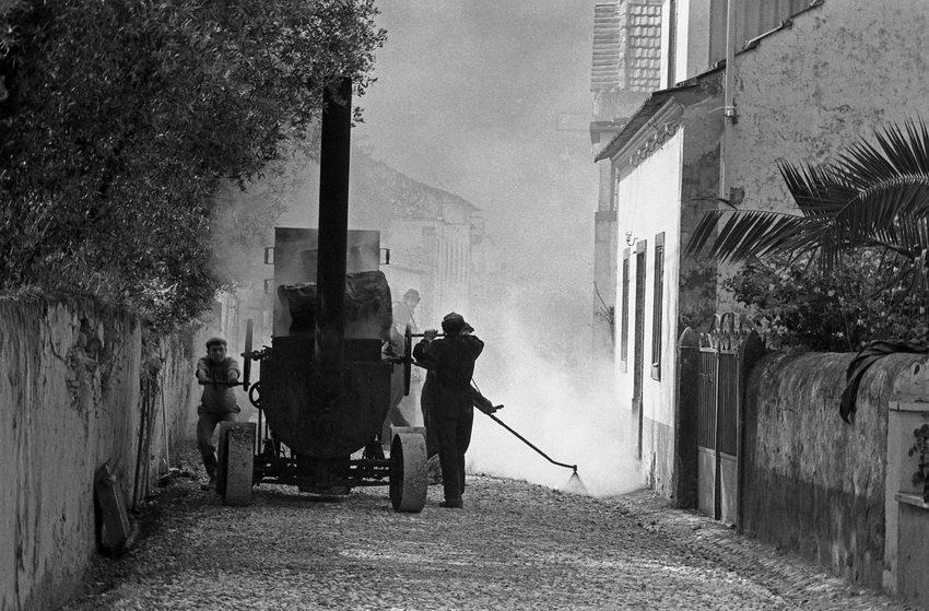 Máquina antiga de alcatroar, movida a manivela pelos trabalhadores