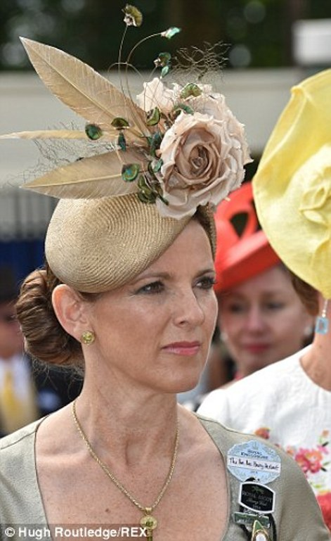 a lady a neat brown cocktail hat enlivened with silk roses and feathers on day 4 of Royal Ascot 2014