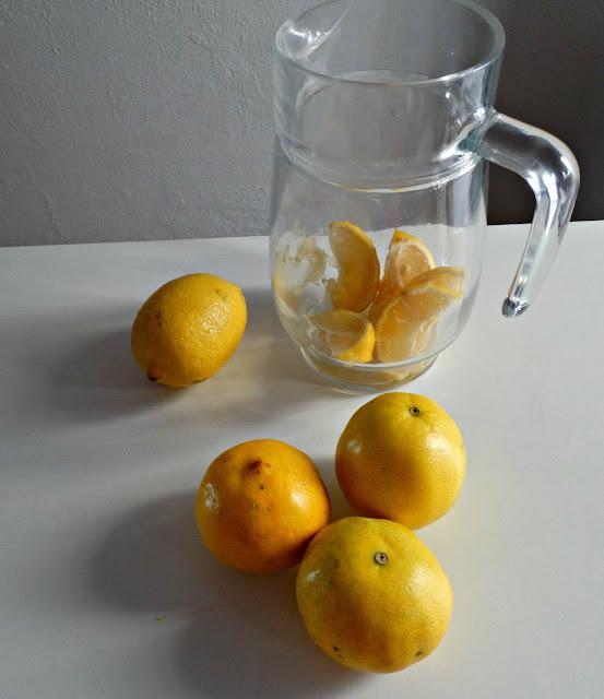 Jarra con una lima cortada en cuartos y tres limas y limón para exprimir