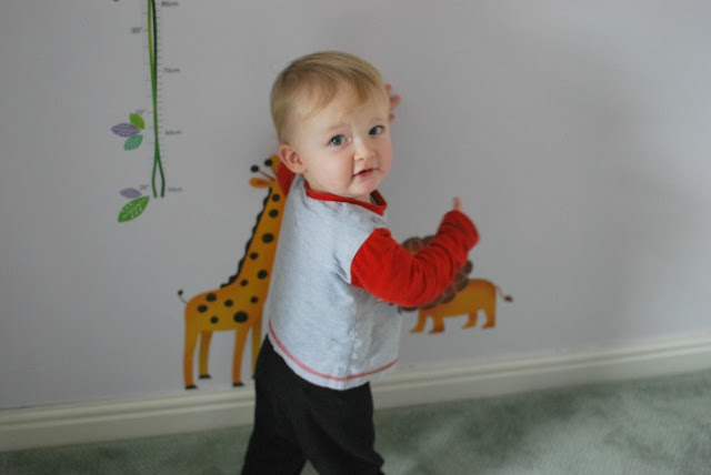 toddler looking at camera pointing to wall stickers