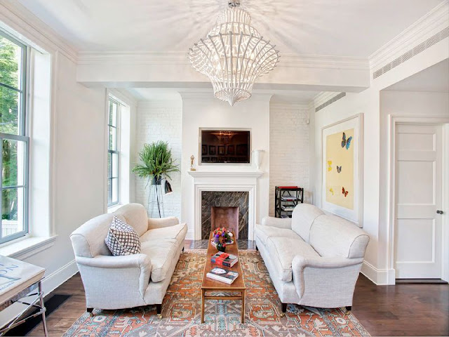 Dueling sofas in front of a marble fireplace with a long wooden coffee table between them, an area rug and a white chandelier