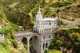 Santuário de Las Lajas Descrição: A fotografia colorida mostra  a Basílica, construida no início do século XX, a igreja é de pedra  em branco e cinza, o  estilo arquitetônico,  neogótico e é  composta por três naves construídas em uma ponte de dois arcos sobre o rio e no passeio, forma um átrio ou praça da  basílica, unindo-se com o outro lado do canyon.A altura do templo, desde a sua base até a torre é de 100 metros, e a ponte é de 50 metros  de altura por 17 metros de largura e 20 metros de comprimento.A extensão do edifício principal é de  quase 30 metros e 15 de largura.  No interior, as três naves são cobertas por abóbadas. As telhas, são de fibra de vidro,  durante o dia, a luz é filtrada através das janelas.  O fundo das três naves é a parede de pedra natural do canyon e na nave principal, encontra-se em uma laje, a pintura da imagem da Virgen  del Rosario. A base do próprio templo, além dos dois arcos da ponte, é uma cripta românica, de três naves cobertas por abóbadas de  estrutura de pedra de cantaria e é dedicado ao Sagrado Coração de Jesus.