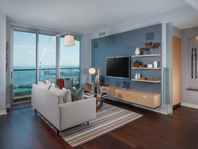Picture of small contemporary living room with white sofa and large tv on the blue wall