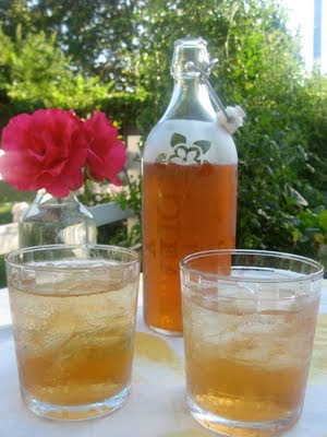 Herbal tea in a glass jar and two glasses of iced tea.