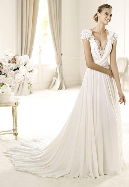 Сватбена рокля с драперии, дълбоко деколте и късо ръкавче от дантела