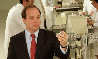 publicity photograph showing man in dark business suit holding a vial of medicine with laboratory workers behind him