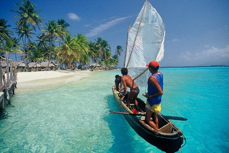 praia de areia branca com casas de palha, vegetação e canoa com nativos