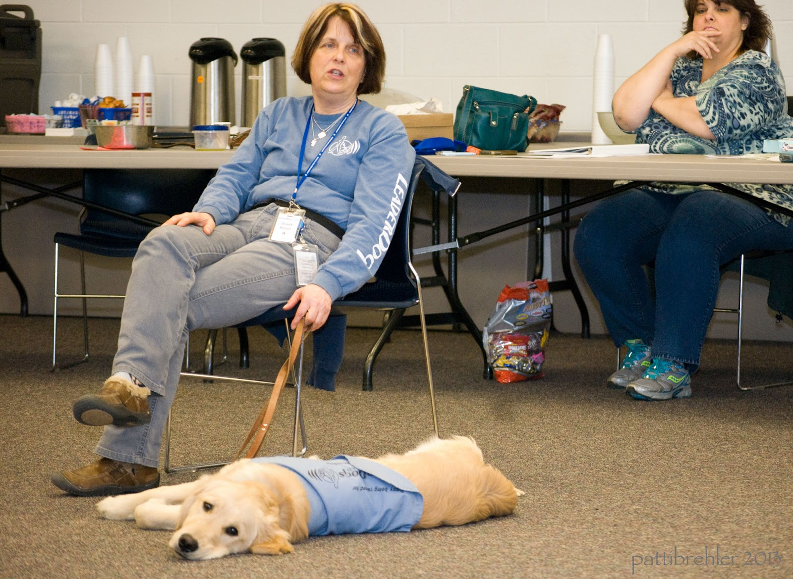 A golden retriever is lying flat on his side on a brown carpet, looking at the camera, he is wearing a baby blue jacket. A woman sitting on a chair behind the dog is holding a brown leash lightly in her left hand at her side. She is wearing a blue long sleeve t-shirt and gray pants. Her legs are crossed and her right hand is on her right thigh. she has short brown hair and is looking at the camera. Beihind the woman are two long folding tables with coffee thermoses on one. Another woman is sitting behind the table on the right, she is wearing a blue flowered shirt and blue jeans.She has her arms crossed with her right hand near her face.