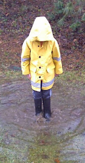 Picture of a little kid with a rain jacket on standing in a puddle